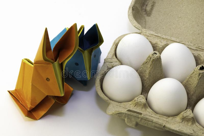 Conigli di origami da carta colorata Lepri di Pasqua ed uova bianche del pollo in una scatola fotografia stock