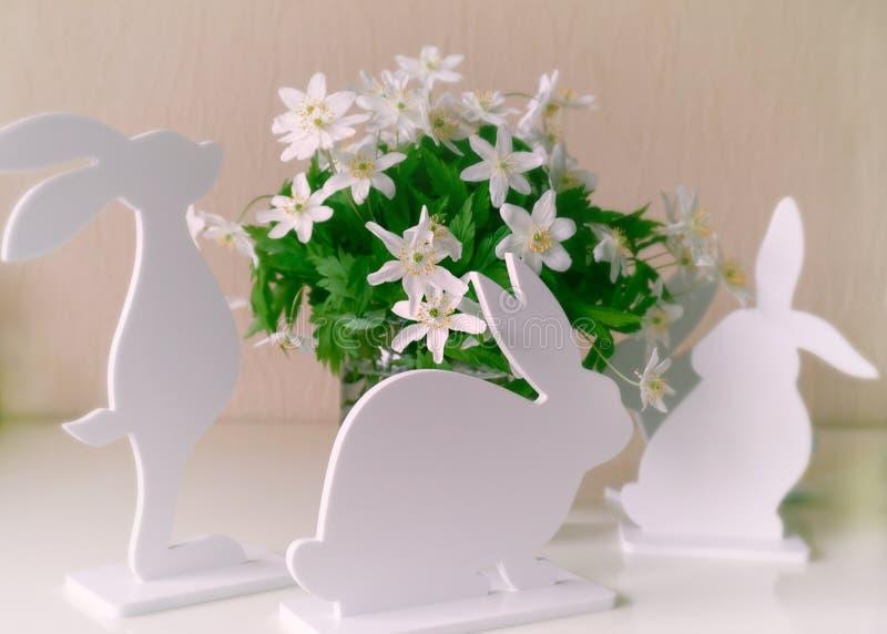 Coniglietti di pasqua con i fiori della molla fotografia stock