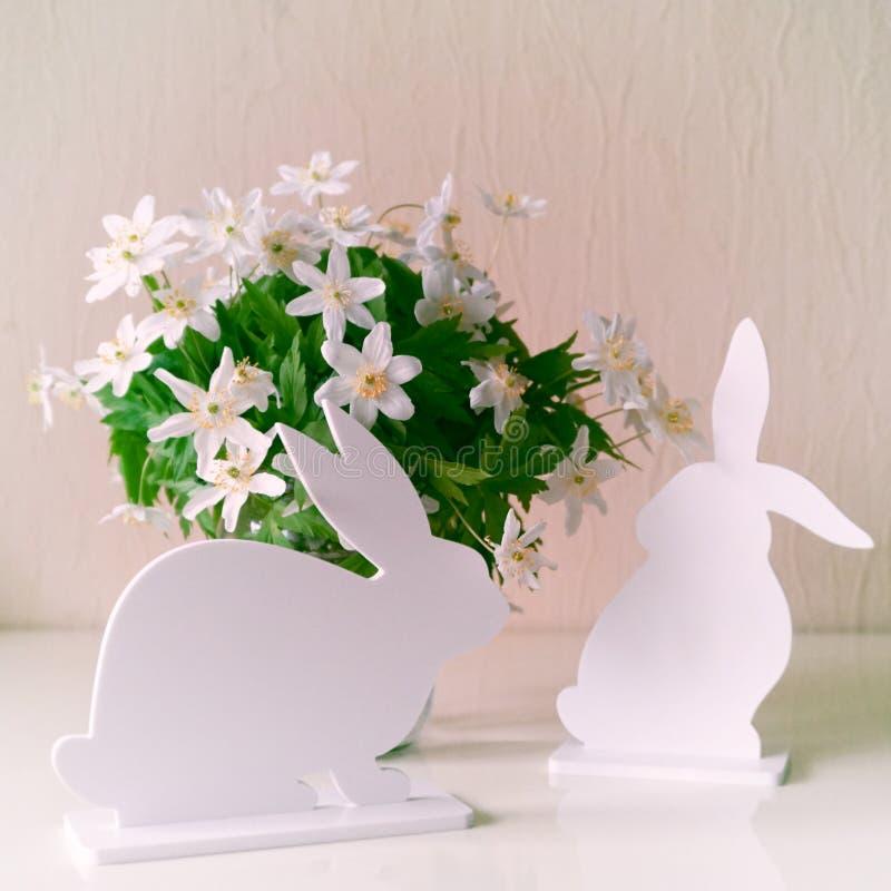 Coniglietti di pasqua con i fiori della molla immagini stock