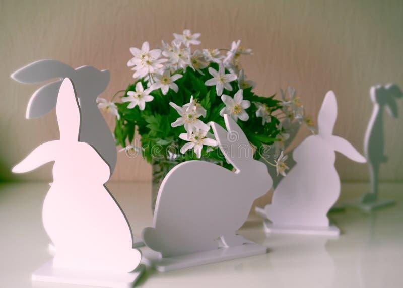 Coniglietti di pasqua con i fiori della molla immagine stock libera da diritti