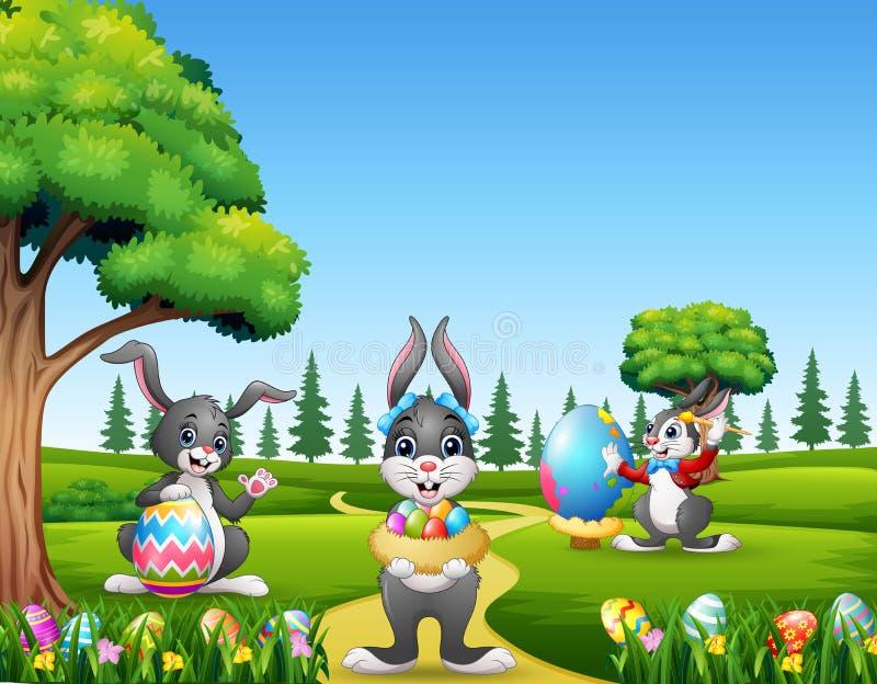 Coniglietti di pasqua felici che tengono e che dipingono le uova immagini stock