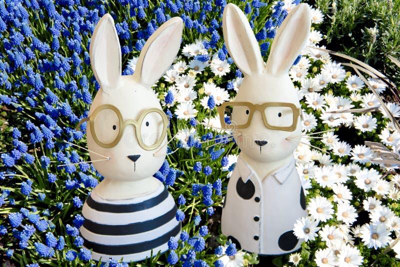 Coniglietti di pasqua in giacinti dell'uva blu, anemoni bianchi fotografia stock libera da diritti