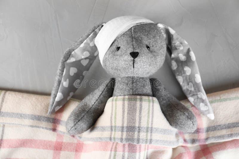 Coniglietto del giocattolo con la fasciatura che si trova sotto la coperta su fondo grigio, vista superiore ` S dei bambini fotografia stock libera da diritti