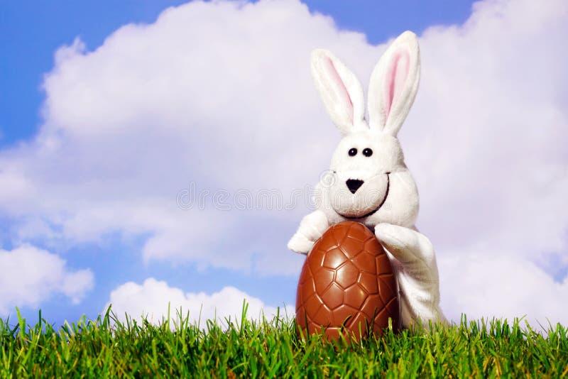 Coniglietto di pasqua che tiene un uovo di cioccolato fotografie stock