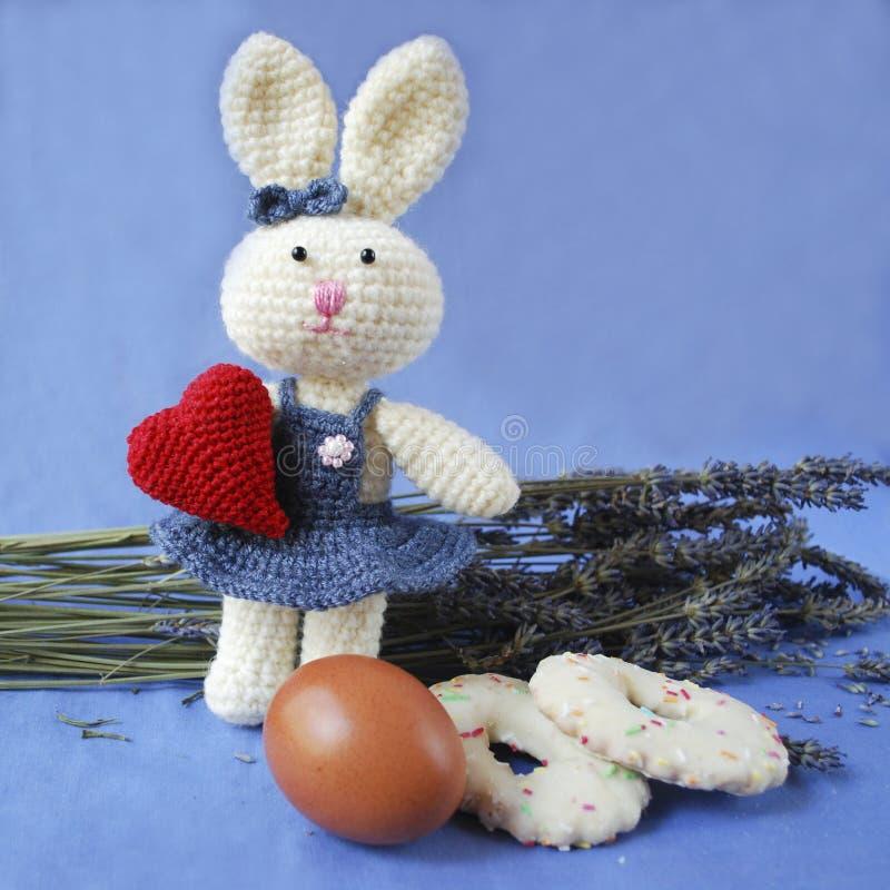 Coniglietto di pasqua con cuore rosso, uovo, biscotti sul fondo della lavanda fotografia stock libera da diritti