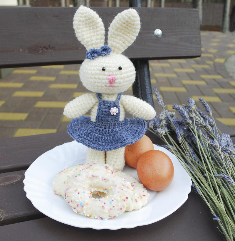 Coniglietto di pasqua con i biscotti sul fondo della lavanda immagini stock libere da diritti