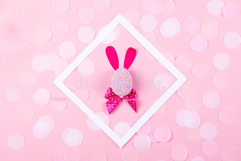 Coniglietto di pasqua con i coriandoli su fondo rosa immagine stock