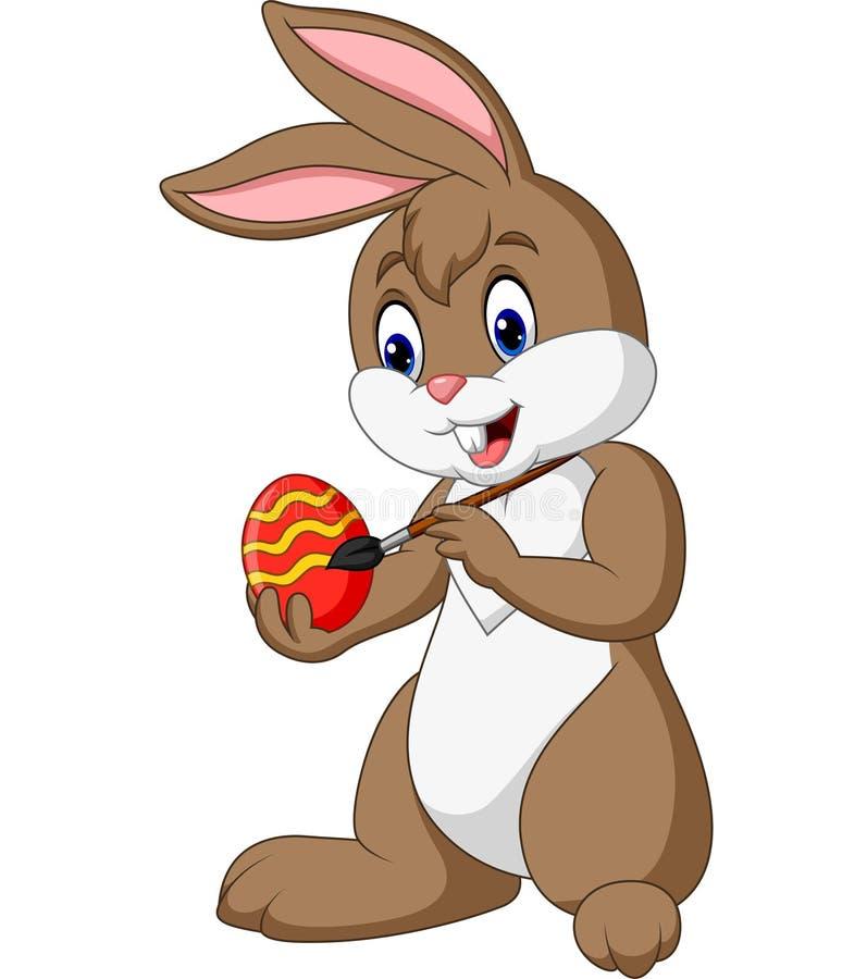 Coniglietto di pasqua divertente del fumetto che dipinge un uovo illustrazione di stock