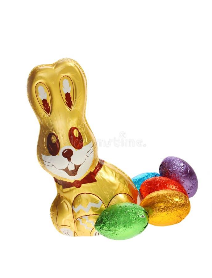 Coniglietto di pasqua dorato del cioccolato con le uova immagine stock