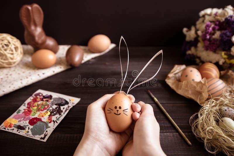 Coniglietto orientale Mani femminili che tengono l'uovo di Pasqua sulla tavola di legno fotografia stock