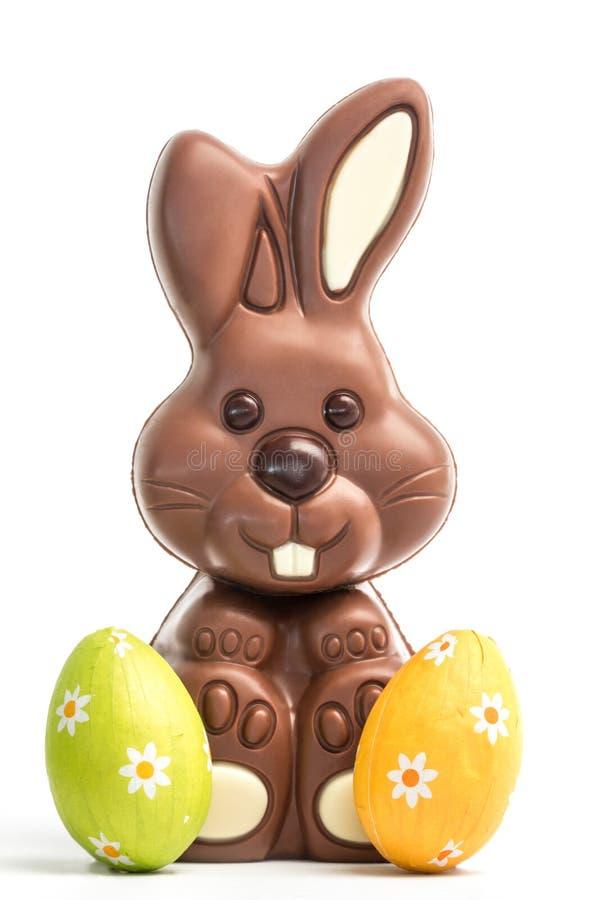 Coniglietto sveglio del cioccolato con due uova di Pasqua immagini stock