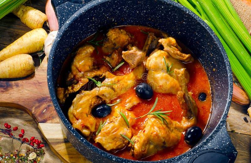 Coniglio al forno in salsa al pomodoro con le olive nere e le erbe fresche fotografia stock
