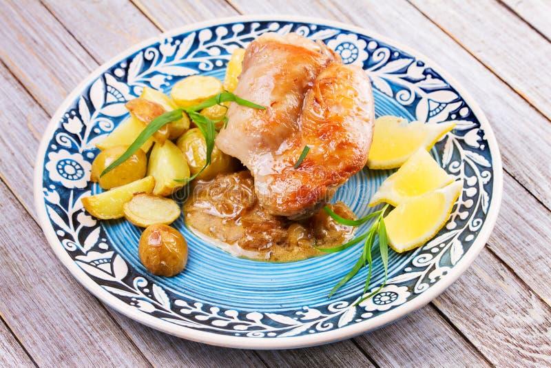 Coniglio con le patate ed il limone in salsa crema, guarnita con dragoncello fotografie stock libere da diritti