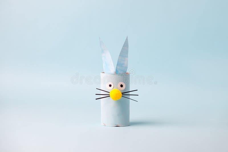Coniglio di coniglio di carta per una festa stagionale di Pasqua felice Facile artigianato per bambini su sfondo blu, semplice id fotografie stock
