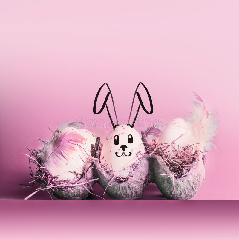 Coniglio di coniglietto di pasqua dipinto sulle uova a fondo rosa pastello fotografia stock libera da diritti