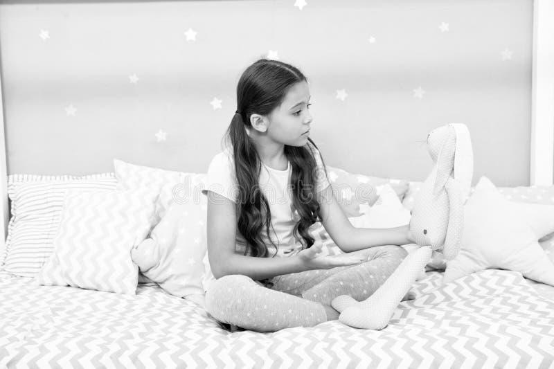 Coniglio di grey del gioco da bambini Migliori amici La ragazza si siede il letto con il coniglietto grigio gioca la sua camera d fotografia stock
