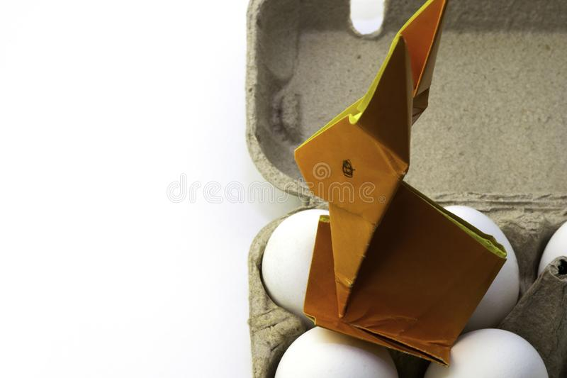 Coniglio di origami da carta arancione Coniglietto di pasqua ed uova bianche del pollo in una scatola, spazio della copia immagine stock libera da diritti