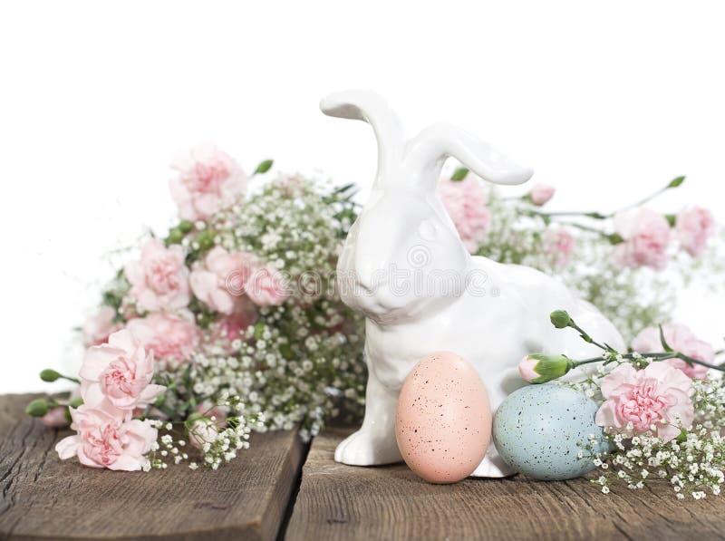 Coniglio di Pasqua con i garofani rosa immagini stock libere da diritti