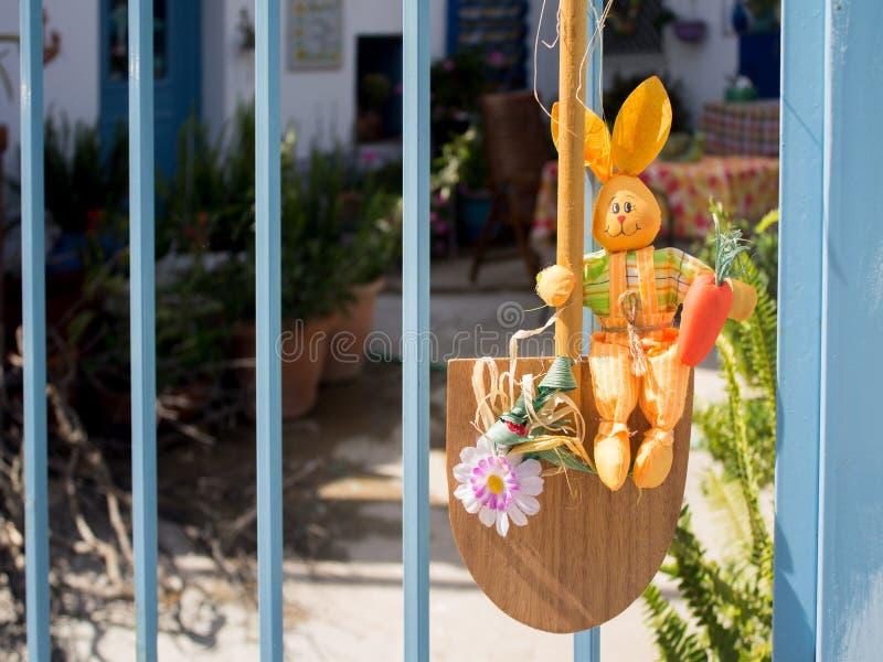Coniglio giallo di Pasqua che si siede su una pala all'entrata all'iarda fotografia stock