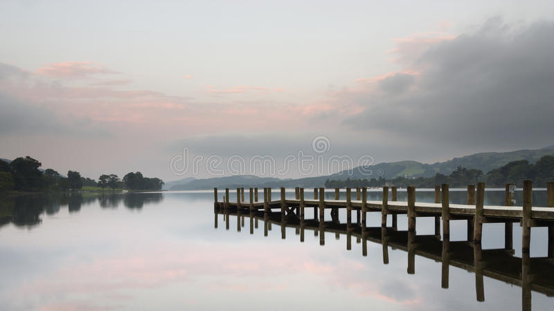Wooden Jetty at lake Coniston, Cumbria. With a beautiful pastel sky reflecting in the still water royalty free stock photography