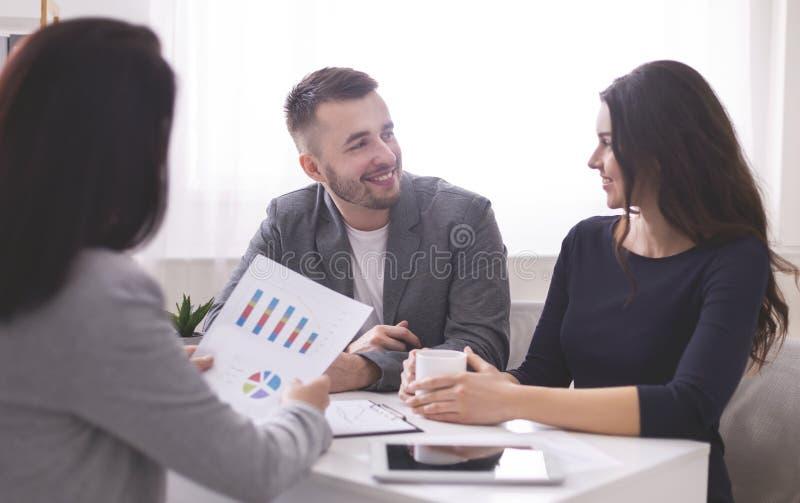 Coniugi felici all'incontro con un consulente finanziario in banca fotografia stock