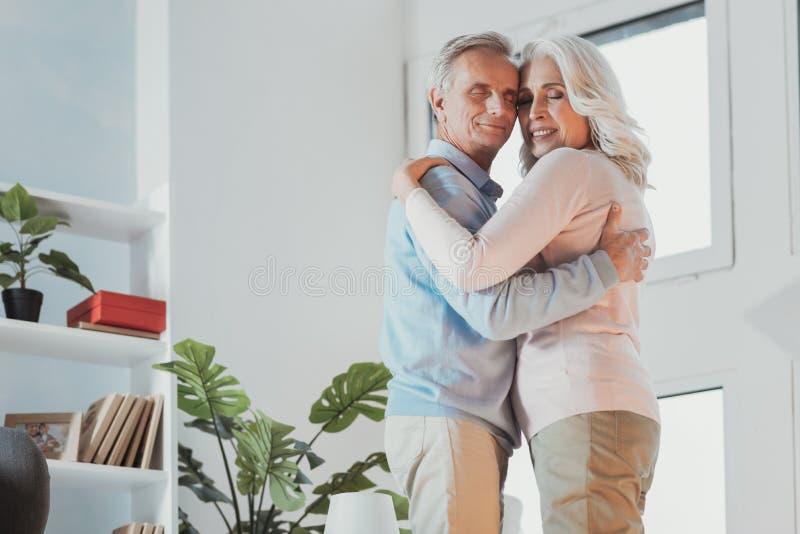 Coniugi senior allegri che abbracciano e che ballano immagine stock libera da diritti
