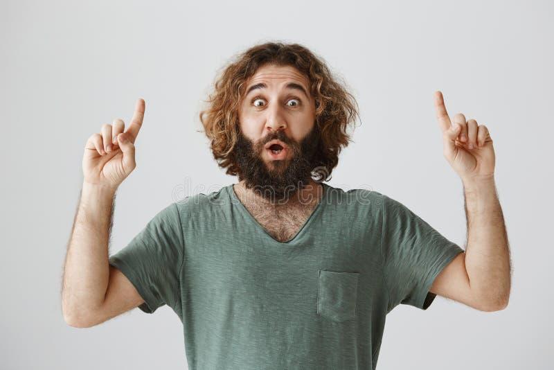Conjecture ce que j'ai vu vers le haut Portrait du type adulte choqué et enthousiasmé avec la barbe et les cheveux bouclés se dir photo stock