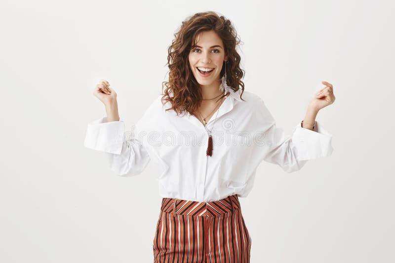 Conjetura que consiguió la promoción Retrato de la mujer apuesta confiada y contenta feliz con el pelo marrón rizado, sonriendo fotografía de archivo