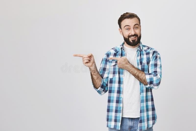 Conjoint adulte beau avec la barbe et la moustache, souriant et exprimant l'acclamation tout en se dirigeant à gauche avec deux m image libre de droits