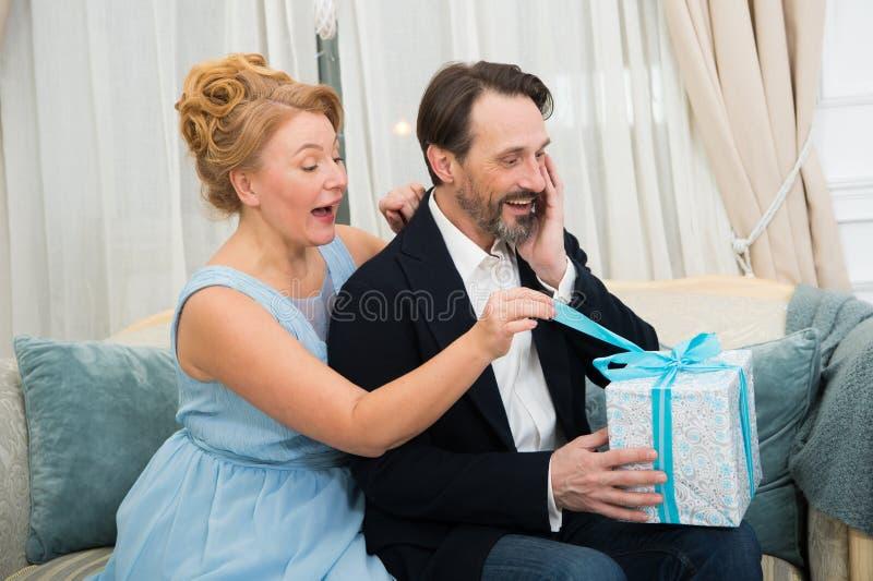Conjoints étonnés déliant le ruban bleu sur le présent photo stock