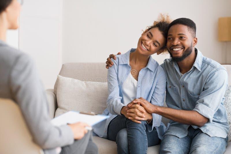 Conjoints d'Afro étreignant heureusement après la réconciliation sur la consultation matrimoniale photographie stock