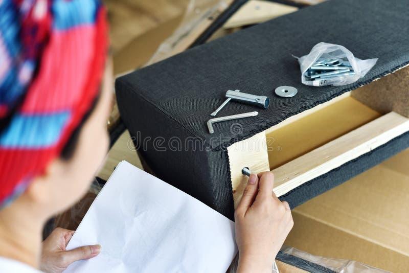 Conjunto da mob?lia, mulher que olha o manual do conjunto da mob?lia fotos de stock royalty free