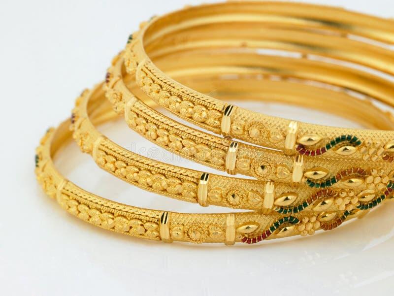 Conjunto de brazaletes diseñados del oro fotografía de archivo libre de regalías