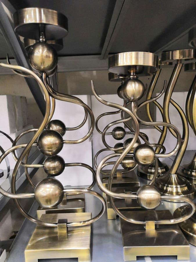 Conjunto de candelabros de bronce de época sobre una mesa blanca interior imágenes de archivo libres de regalías
