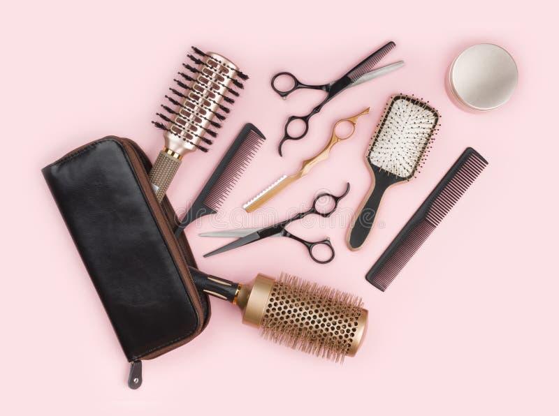 Conjunto de ferramentas do armário do cabelo com o saco de couro no fundo cor-de-rosa imagem de stock royalty free
