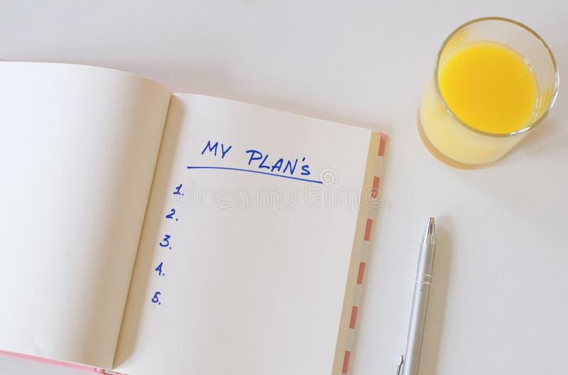 Conjunto de la oficina tel?fono, jugo, pluma, tel?fono y diario mis planes, espacio para el texto Fondo blanco fotografía de archivo