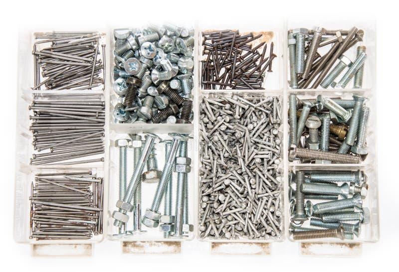 Conjunto de tornillos y de clavos en blanco imágenes de archivo libres de regalías