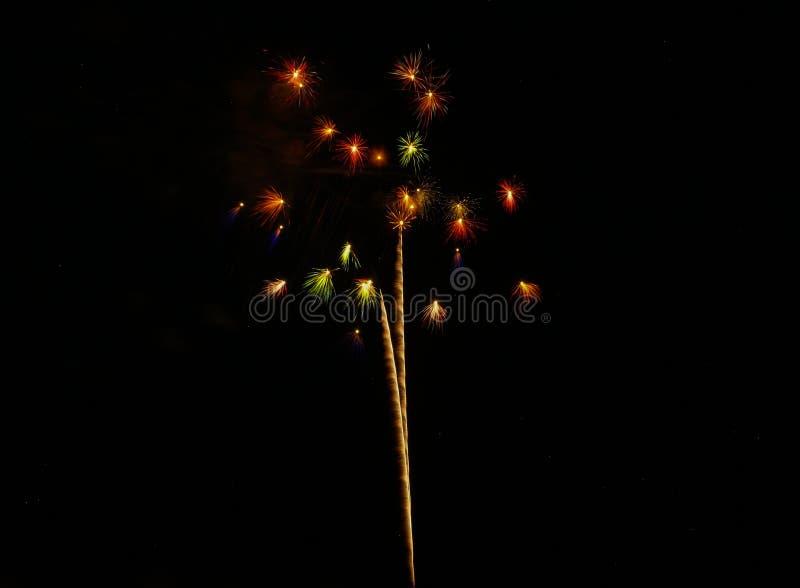 Conjunto de vermelho, de verde, e de explosões pequenos do ouro contra um céu preto no quarto de julho fotos de stock royalty free