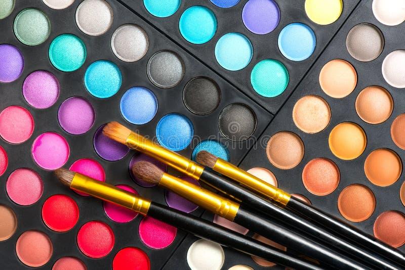 Conjunto del maquillaje Multicolores profesionales componen la paleta y cepillos de los sombreadores de ojos fotografía de archivo