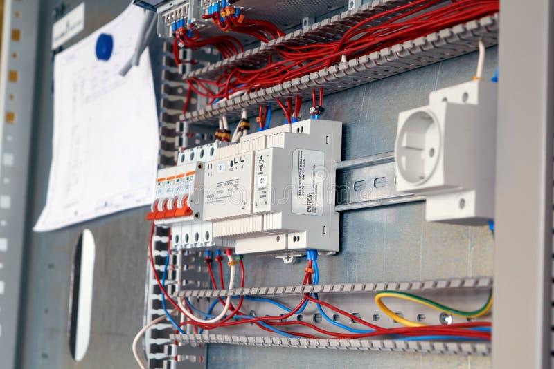 Conjunto do armário bonde de acordo com o esquema Interruptores, fios fotografia de stock