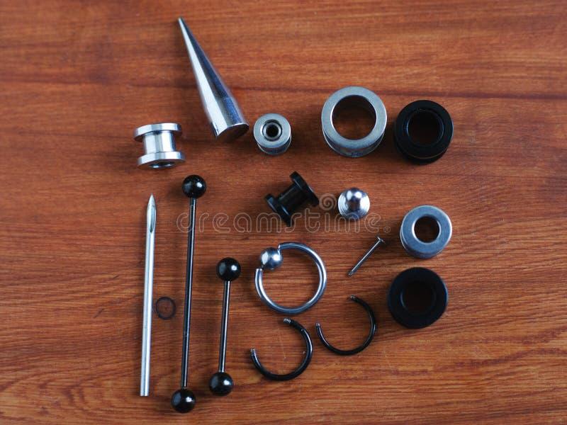 Conjunto para acessórios de perfuração em fundo de madeira um cateter para a língua, uma vara na língua e sobrancelhas, brincos fotografia de stock
