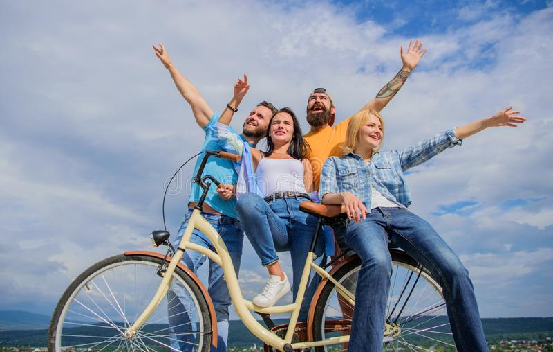 Conmutación urbana de la libertad La gente joven elegante de la compañía gasta el fondo del cielo del ocio al aire libre Biciclet foto de archivo libre de regalías