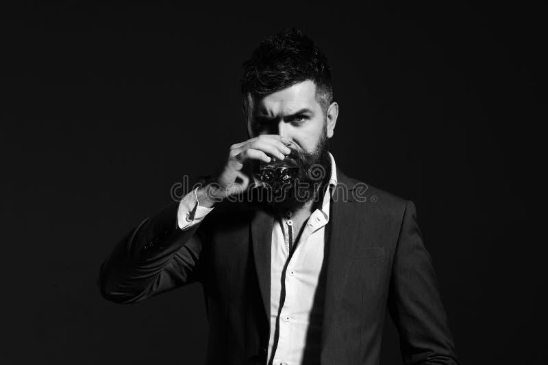 Connaisseur avec la barbe et le bourbon ou le whiskey sur le fond noir images libres de droits