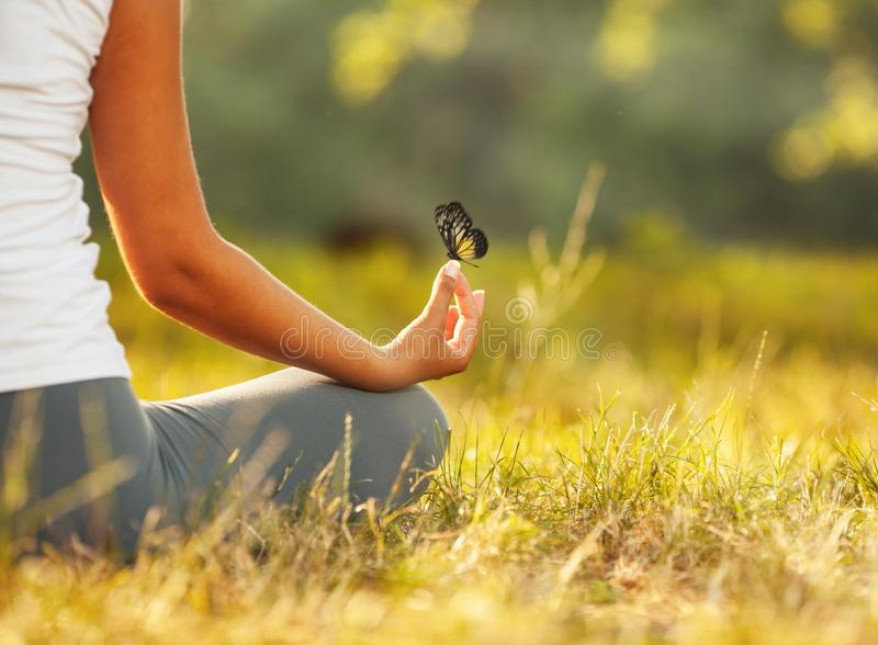 Connected with nature.Butterfly. Young woman practicing morning meditation in nature at the park. Connected with nature stock images