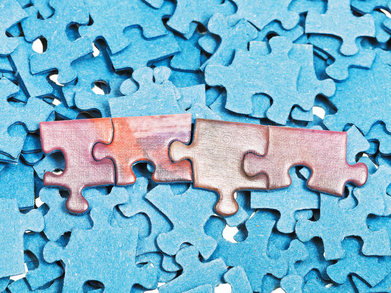 Connected pieces on pile of blue jigsaw puzzles. Few connected pieces on pile of blue jigsaw puzzles royalty free stock photo