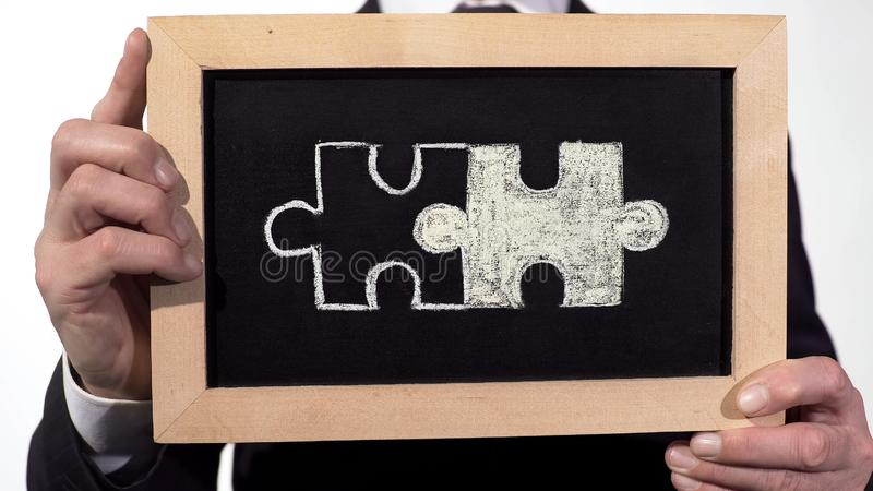 Connected puzzles drawn on blackboard in businessman hands, partnership symbol royalty free stock images