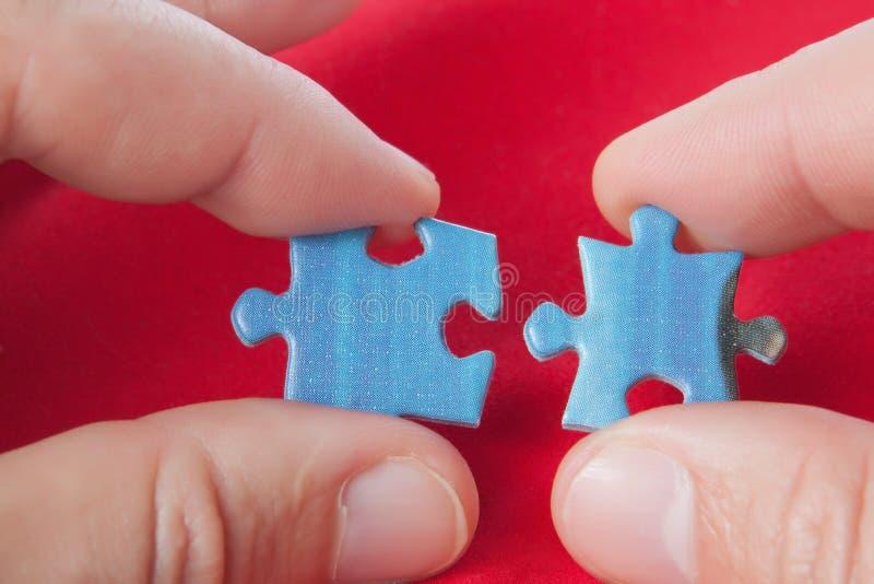 Connecter deux puzzles. photographie stock