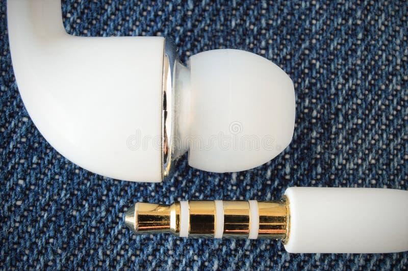 Connecteur blanc de cric d'écouteurs sur le fabricbackground de jeans images libres de droits