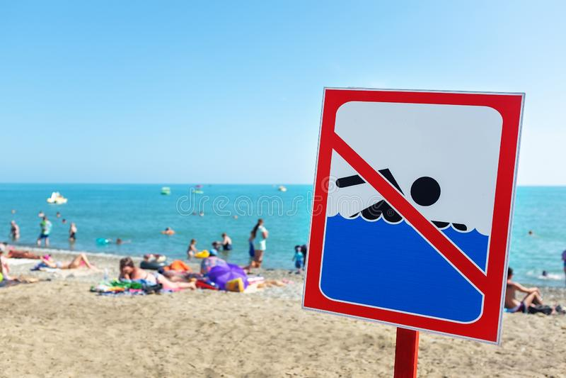 Connectez-vous la plage n'est pas laiss? nager ! Les gens se baignent et se reposent sur la mer malgr? le signe et l'interdiction image libre de droits