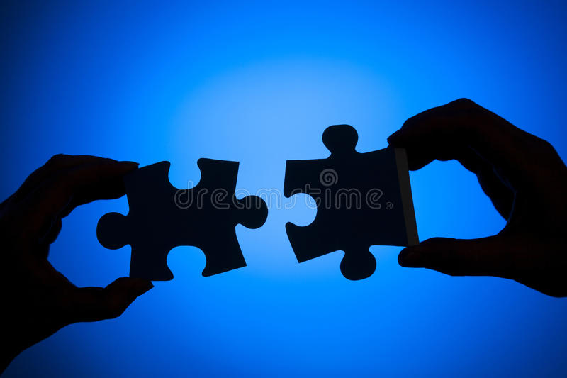 Connecting. Silhouette of two hands connecting pieces of a puzzle on a blue background stock image